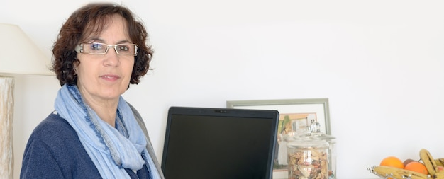 Rijpe vrouw met laptop in haar huis