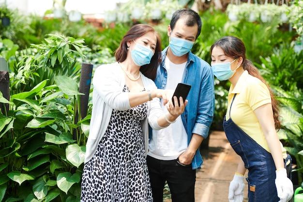 Rijpe vrouw met medisch masker die foto van bloem op smartphone toont en arbeiders vraagt om haar te helpen bij het vinden ervan op de plantenmarkt