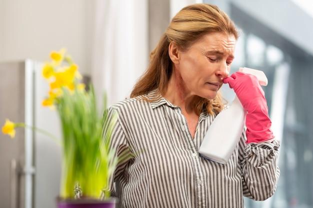 Rijpe vrouw met rimpels in het gezicht voelt zich slecht en lijdt aan allergie tijdens het schoonmaken van flat