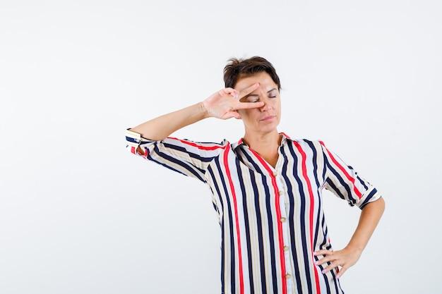 Rijpe vrouw met v-teken op oog terwijl ze de ogen sluit, hand op taille in gestreepte blouse vasthoudt en kalm kijkt. vooraanzicht.