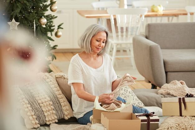 Rijpe vrouw met warme sjaal in haar handen tijdens het openen van cadeautjes tijdens kerstavond thuis