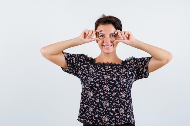 Rijpe vrouw ogen openen met vingers in bloemenblouse, zwarte rok en vrolijk kijken. vooraanzicht.