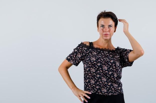 Rijpe vrouw poseren terwijl het houden van handen op taille in blouse en op zoek aantrekkelijk, vooraanzicht.