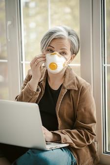 Rijpe vrouw rechtzetten van het masker werkt laptopcomputer zittend op een vensterbank.