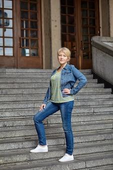 Rijpe vrouw staat op trappen bij ingang van openbaar gebouw in europese stad.