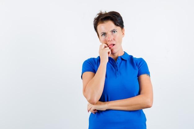 Rijpe vrouw tong uitsteekt terwijl ze in blauw t-shirt denkt en verbaasd kijkt. vooraanzicht.