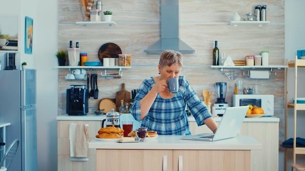 Rijpe vrouw typen op laptop in de keuken tijdens het ontbijt en koffie drinken. oudere gepensioneerde die vanuit huis werkt, telewerken met behulp van externe internetbaan online communicatie over moderne technologie