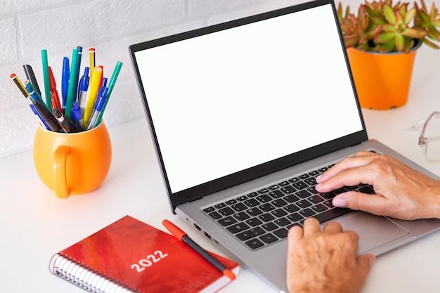 Rijpe vrouw typen op toetsenbord met behulp van laptopcomputer witte desktop en bakstenen muur sociaal werk