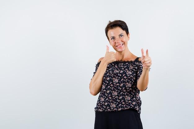 Rijpe vrouw wijzend op camera met wijsvinger, duim opdagen in bloemenblouse, zwarte rok en op zoek vrolijk, vooraanzicht.