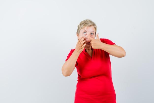 Rijpe vrouw wijzend op haar ooglid getrokken door vinger in rood t-shirt