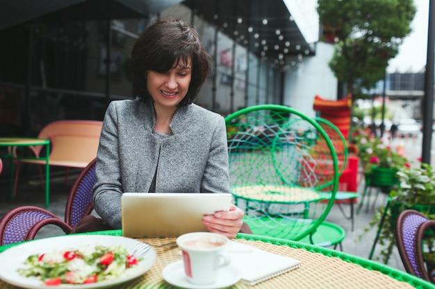 Rijpe vrouw zit alleen in café of restaurant
