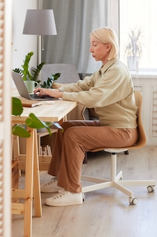 Rijpe vrouw zit op haar werkplek thuis en werkt op een laptop computer