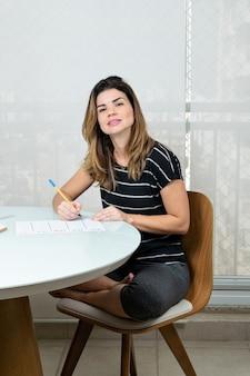 Rijpe vrouw zittend met gekruiste benen schrijven en staren naar de camera