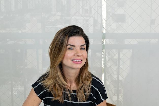 Rijpe vrouw zittend op de bank lachend in een gestreept overhemd en met een glad gordijn op de achtergrond
