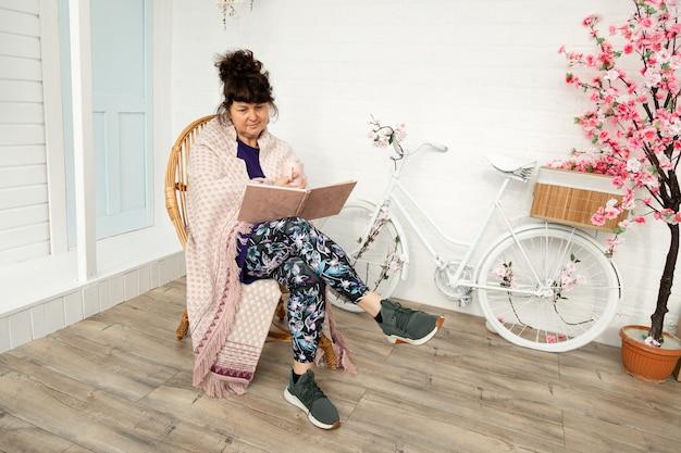 Rijpe vrouw zittend op rieten stoel in de achtertuin thee drinken en boek lezen. kamperen en ontspannen in de tuin.