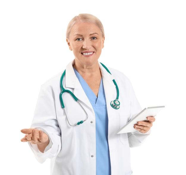 Rijpe vrouwelijke arts met tabletcomputer op wit