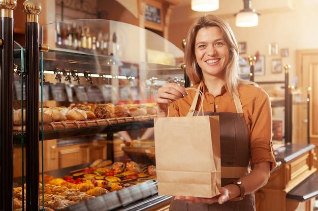 Rijpe vrouwelijke bakker die bij haar bakkerijopslag werkt