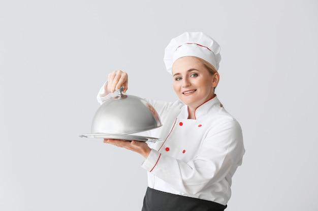 Rijpe vrouwelijke chef-kok met dienblad en cloche