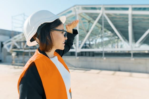 Rijpe vrouwelijke ingenieur op bouwwerf