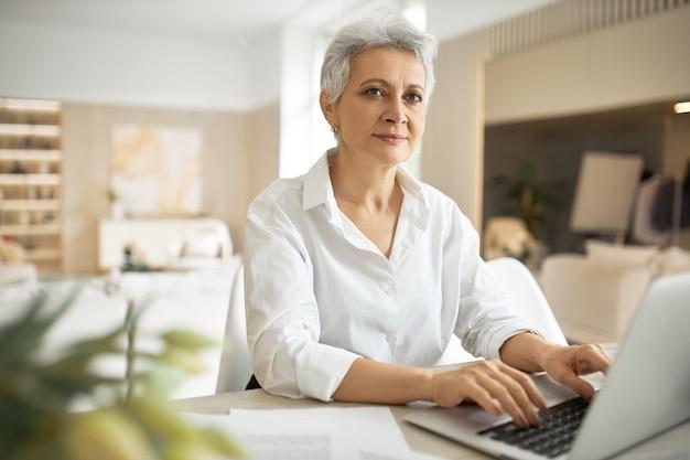 Rijpe vrouwelijke journalist met kort grijs haar typen op laptop, zittend op de werkplek met handen op toetsenbord, gelaatsuitdrukking hebben geïnspireerd