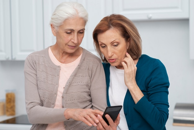 Rijpe vrouwen die een telefoon samen controleren