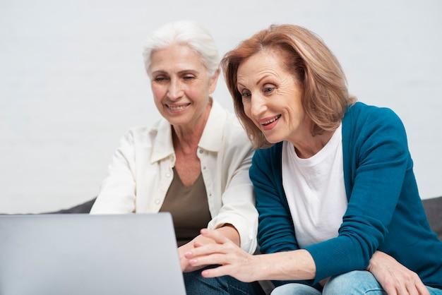 Rijpe vrouwen die op laptop doorbladeren