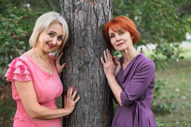 Rijpe vrouwen die samen in het park stellen