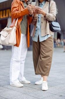 Rijpe vrouwen in stijlvolle kleding houden moderne mobiele telefoons vast op straat in de stad