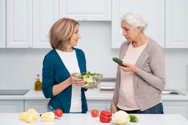 Rijpe vrouwen klaar om samen te koken