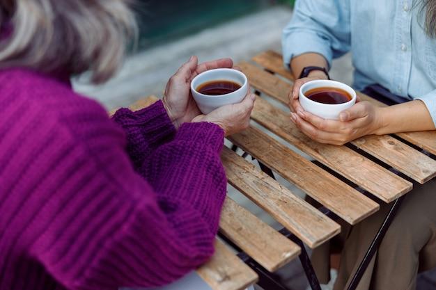 Rijpe vrouwen met kopjes verse koffie zitten aan een houten tafel op het terras van een café