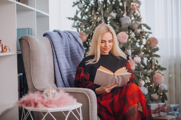 Rijpe vrouwenzitting als voorzitter door kerstmisboom