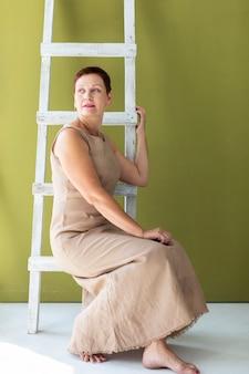 Rijpe vrouwenzitting op een ladder