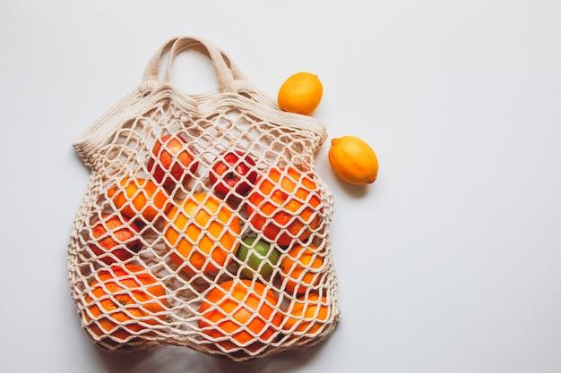 Rijpe vruchten in de gehaakte netzak op de witte ruimte. gezonde levensstijl concept. levering concept.
