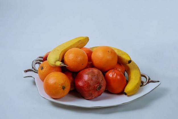 Rijpe vruchten op een wit dienblad op een witte achtergrond