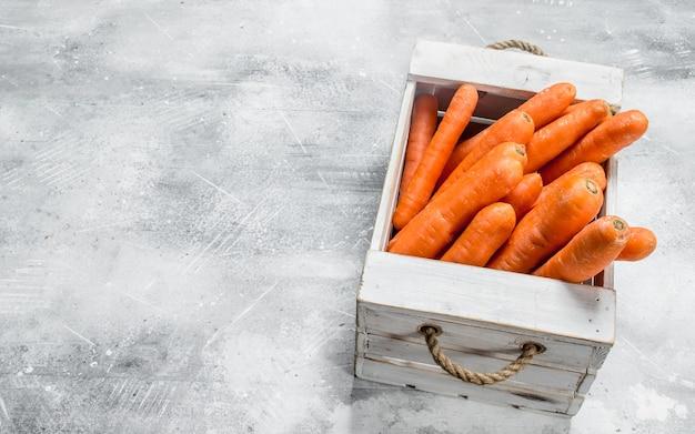 Rijpe wortel in de doos. op rustieke achtergrond