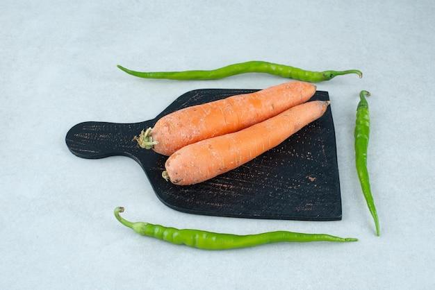 Rijpe wortelen en paprika's op donker bord.