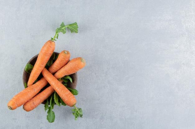 Rijpe wortelen in de kom, op het marmer.