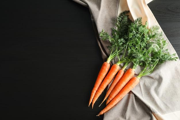 Rijpe wortelen op zwarte tafel, ruimte voor tekst