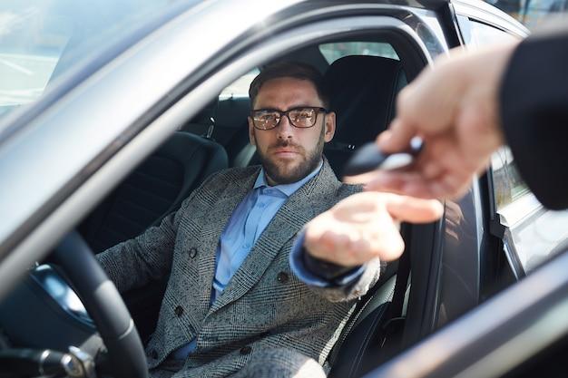 Rijpe zakenman die de auto huurt voor zakenreis die hij sleutels van manager krijgt terwijl hij in autosalon zit
