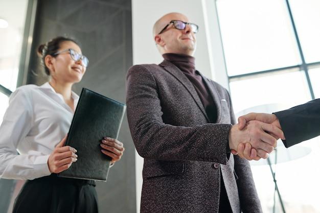 Rijpe zakenman die de hand van zakenpartner schudt na onderhandeling of tijdens begroeting met dichtbij staande secretaris