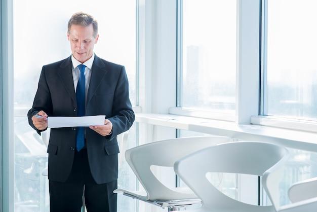 Rijpe zakenman die document in bureau onderzoeken