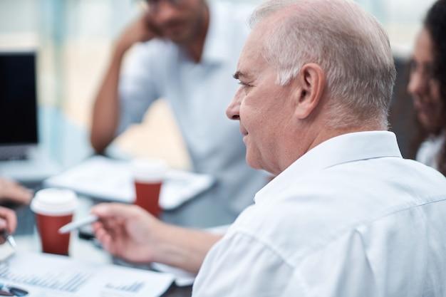 Rijpe zakenman die financiële documenten bespreekt met een werkgroepclose-up