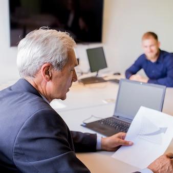 Rijpe zakenman die grafiek in het bureau analyseert