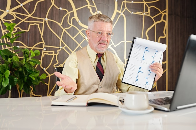 Rijpe zakenman die grafiek met financieel rapport toont wanneer videogesprekken zakenpartner