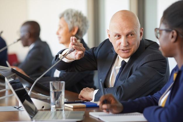 Rijpe zakenman die iets met zijn collega bespreekt tijdens handelsconferentie
