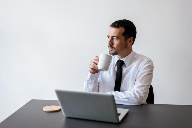 Rijpe zakenman die koffiepauze in bureau neemt