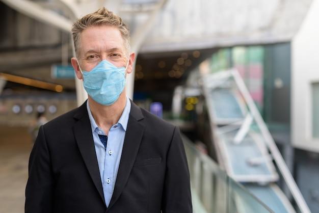 Rijpe zakenman die masker draagt voor bescherming tegen uitbraak van coronavirus bij de voetgangersbrug