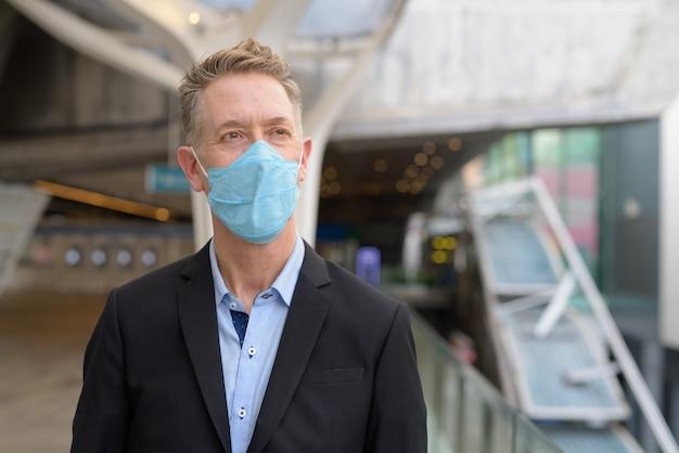 Rijpe zakenman die met masker denkt voor bescherming tegen de uitbraak van het coronavirus bij de voetgangersbrug