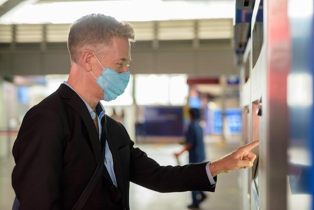 Rijpe zakenman die met masker kaartje kopen bij het hemelstation