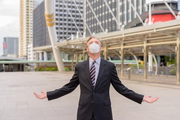 Rijpe zakenman die met masker omhoog met wapens kijkt die bij de skywalk-brug worden opgeheven